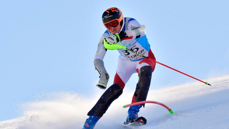 Male standing skier makes  turn