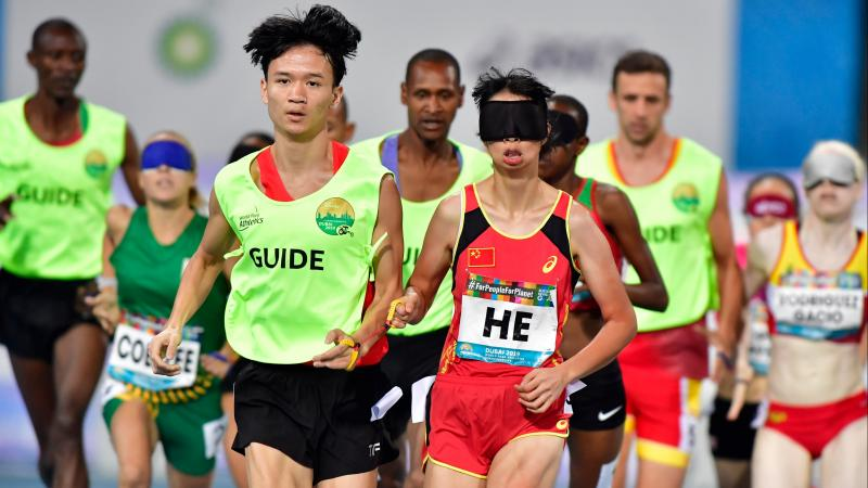 Chinese vision impaired runner with her guide