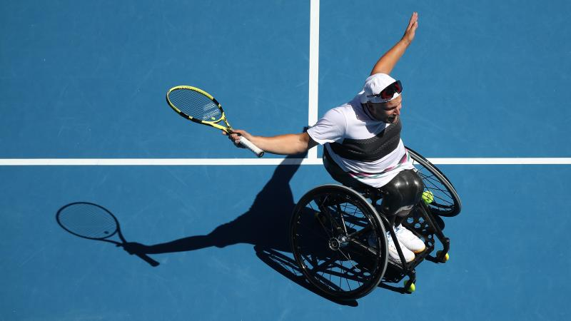 Dylan Alcott on the court extending his arms in celebration while holding the racket