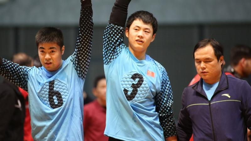 Chinese goalball players lift their arms after a victory