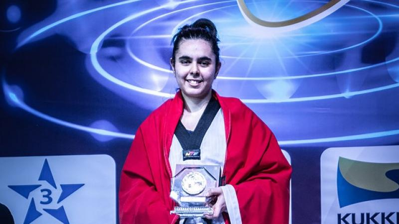 Female taekwondo fighter smiles holding prize