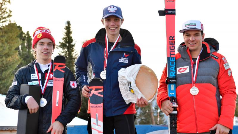 Male standing skiers on the podium