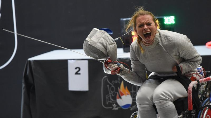 Female wheelchair fencer removes mask to celebrate