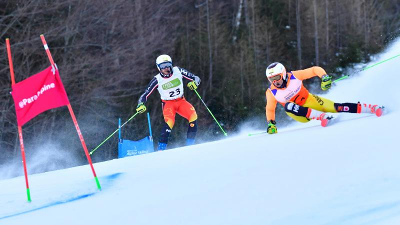 Male alpine skier making a turn with his guide behind him