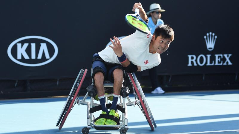 Japanese man in wheelchair hits a return shot in tennis
