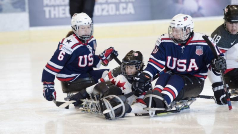 US and Canadian female Para ice hockey players fight for the puck