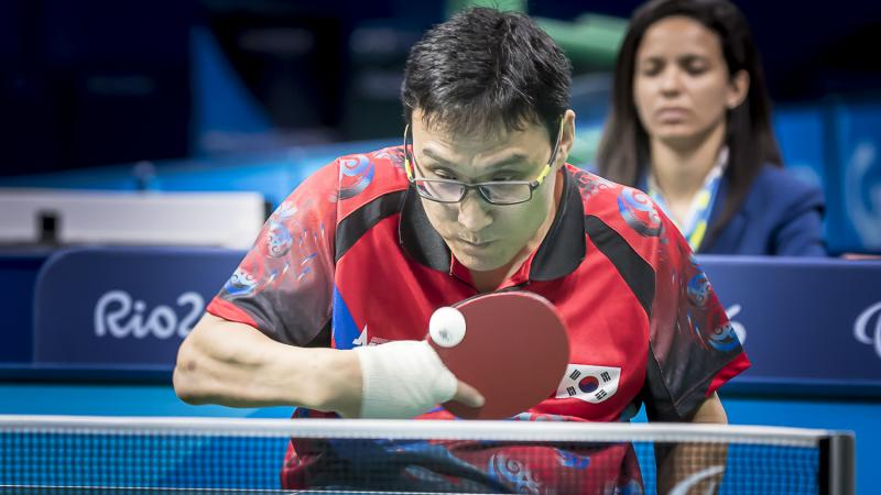 Korean male in wheelchair hits return shot in table tennis