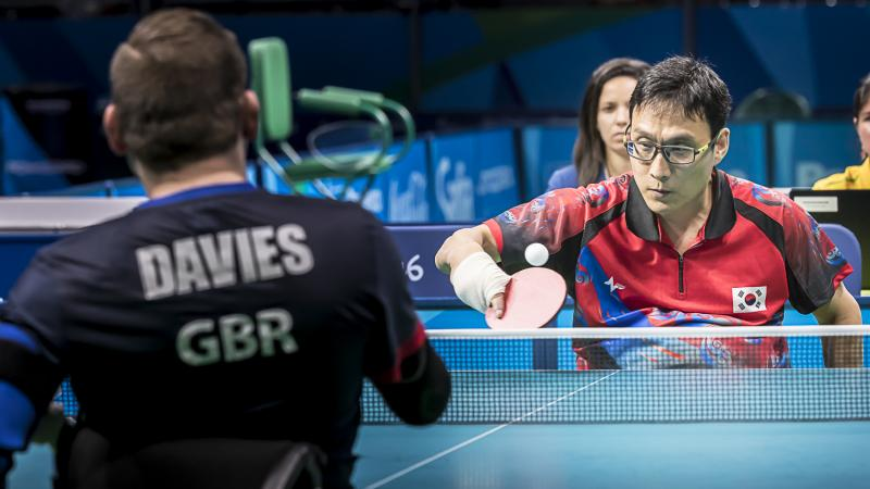 Two men in wheelchairs competing in table tennis