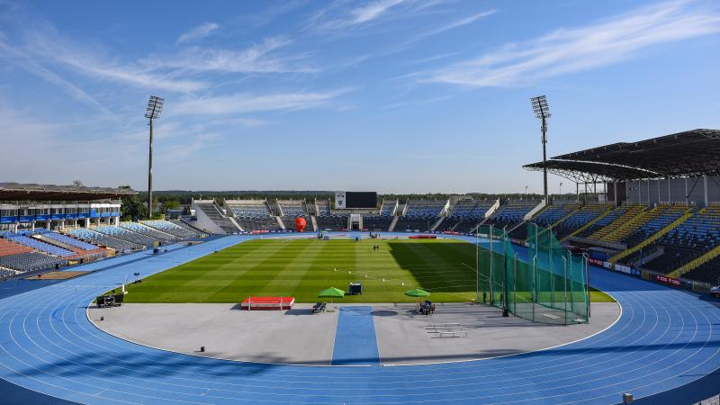 A stadium with a blue athletics track and field