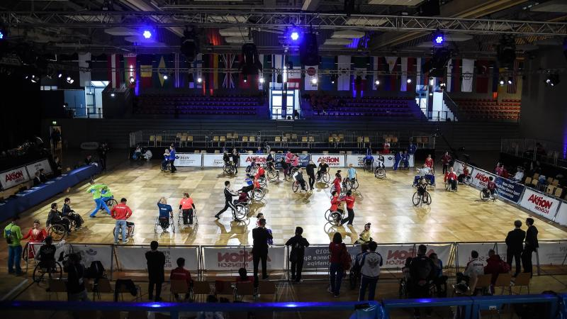 A group of dancers in wheelchairs on a court with their dancing partners