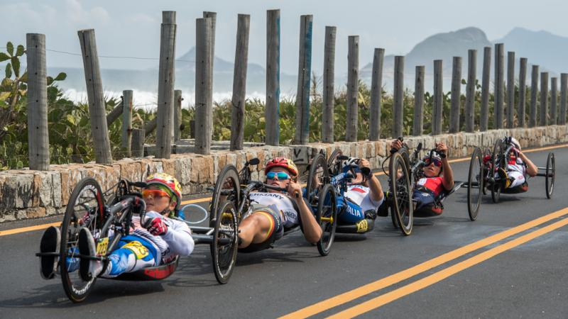 Five female hand cyclist racing in a line