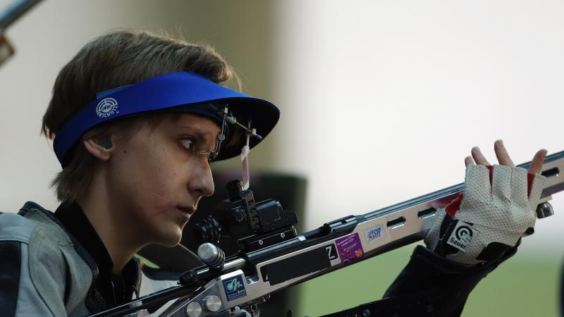 A woman holding a rifle in a shooting Para sport competition