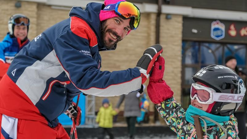 A male Para alpine skier giving a high-five to a little girl in alpine skiing outfit