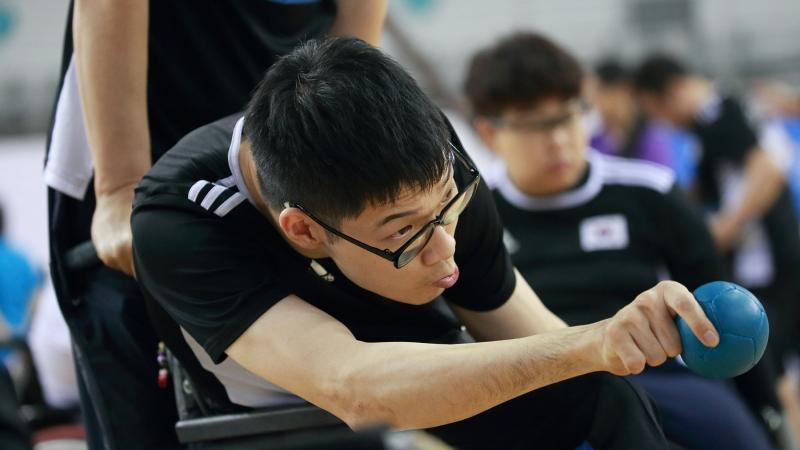 Korean male boccia player about to throw the ball
