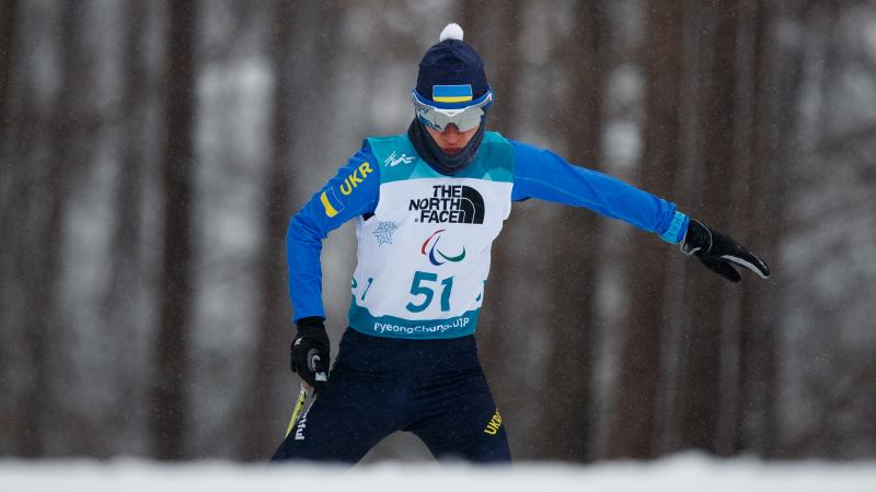 A female standing Para biathlete in the snow