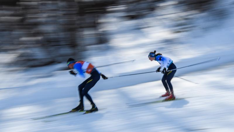A male guide and a female athlete competing in Para biathlon