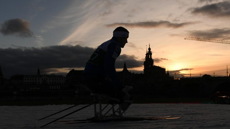 A male sit-skier competing on the snow with the Dresden skyline as background