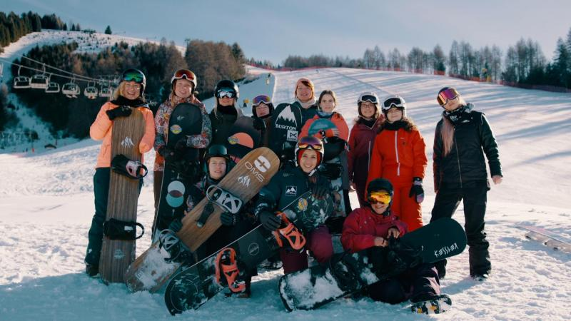 A group of 12 female Para snowboarders posing for picture with their equipment on the snow