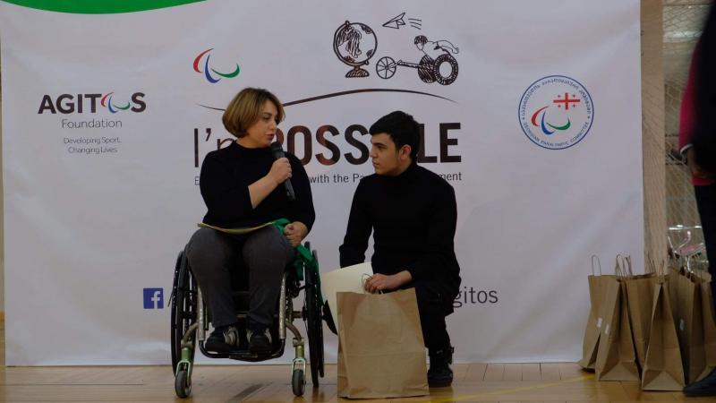 Woman in wheelchair speaks with student winner