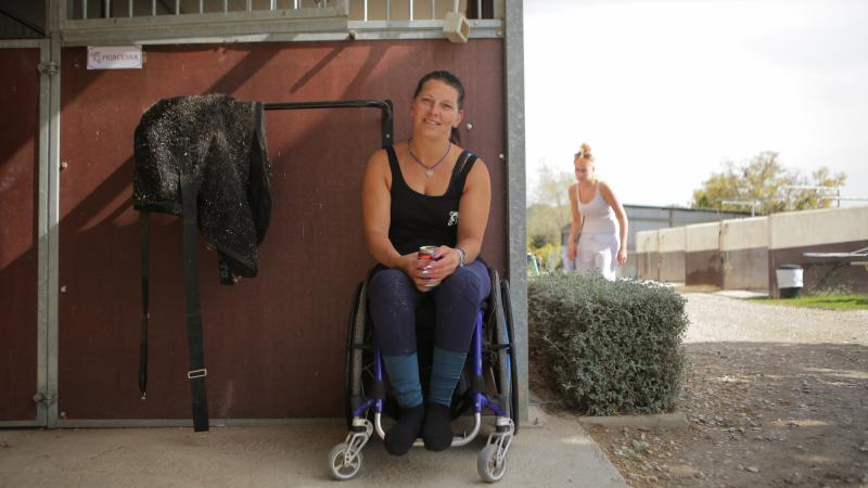 Woman in wheelchair smiles outside a horse stable