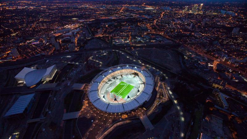 "Aerial view of the London 2012 Olympic stadium with a ""one"" made of green lights in the center"