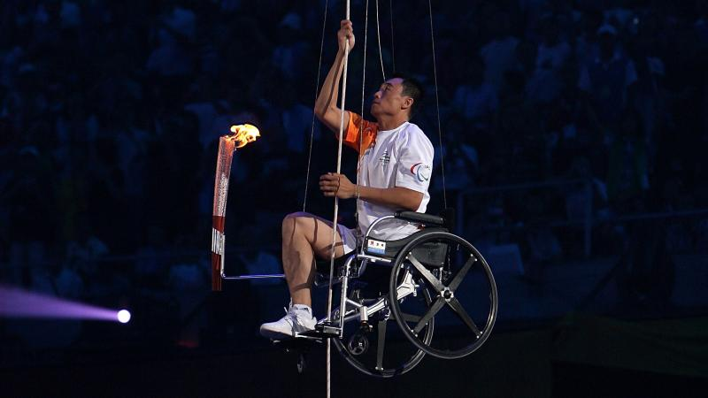 A picture of a man in wheelchair climbing with a torch