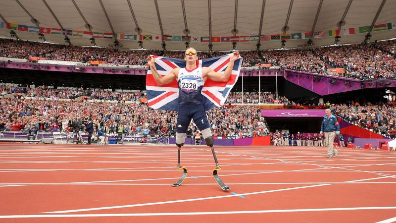 A picture of a man celebrating his victory wearing a flag of Great Britain