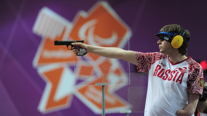 Sergey Malyshev of Russia, wearing glasses, a visor and ear protection shoots his Mixed P3-25m Pistol at an indoor range at The Royal Artillery Barracks