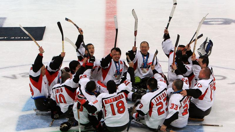 A picture of men playing sledge hockey celebrating their victory