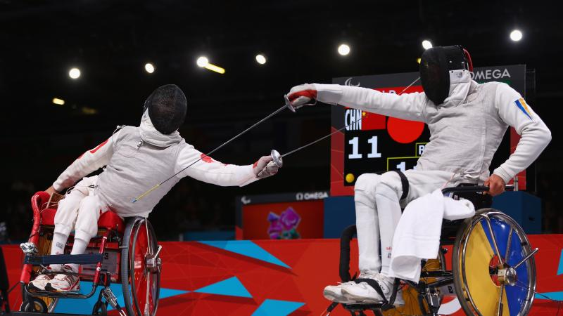 A picture of 2 men in wheelchairs fencing.