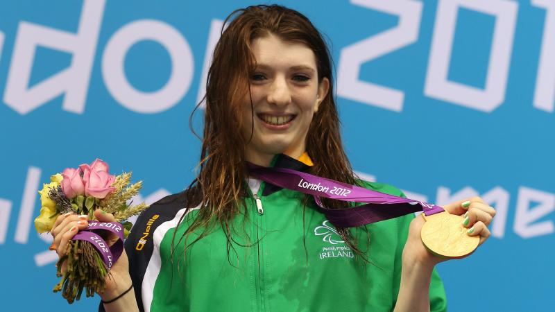 A picture of a woman showing her gold medal