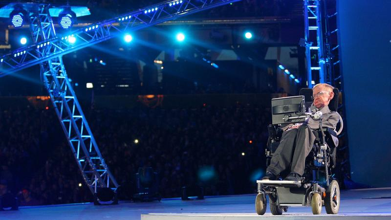 A picture of a man in an electrical wheelchair talking during a ceremony