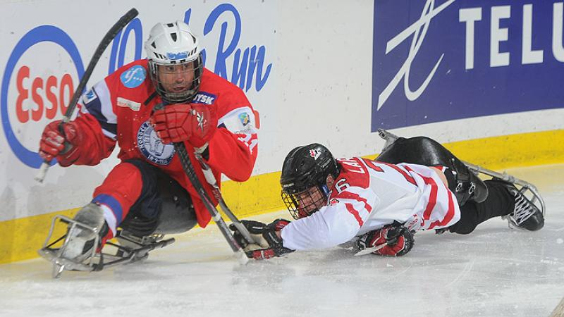 A picture of two men in a sledge playing ice sledge hockey.