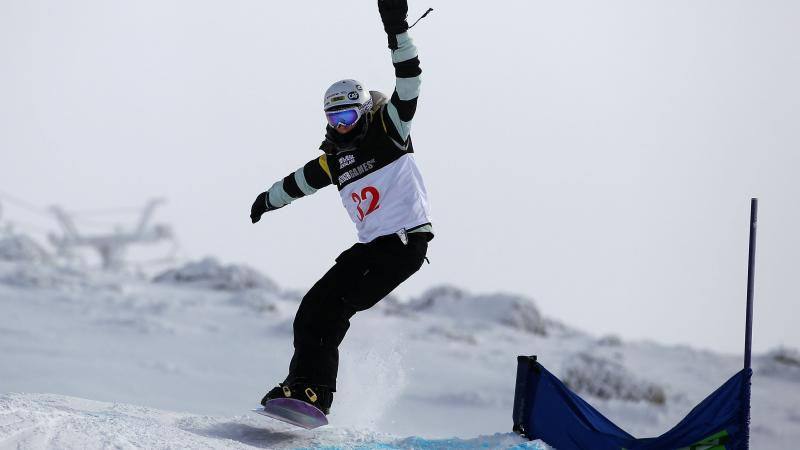 A picture of a woman jumping with a snowboard