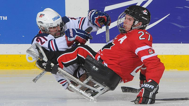 A picture of two men in sledges playing ice hockey