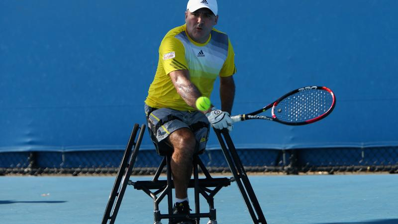 A picture of a man in a wheelchair playing a backhand during a wheelchair tennis match