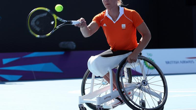 A picture of a woman in a wheelchair playing a forhand during a wheelchair tennis match.