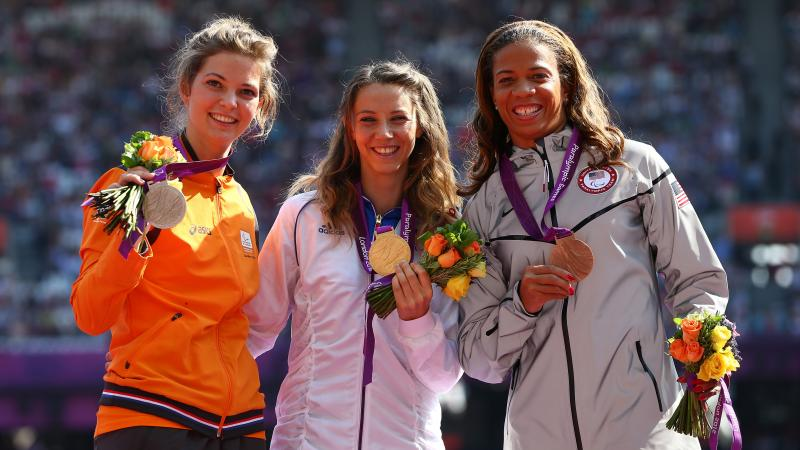A picture of women on a podium with medals around their neck
