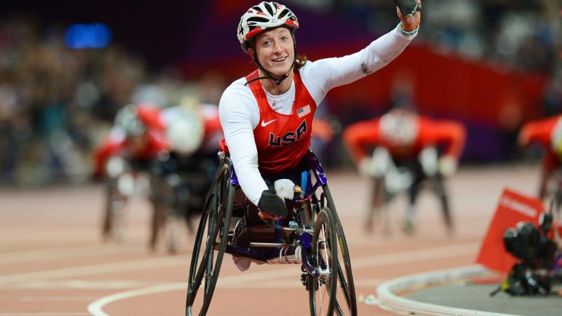 A picture of a woman in the wheelchair on a track celebrating with her hand up