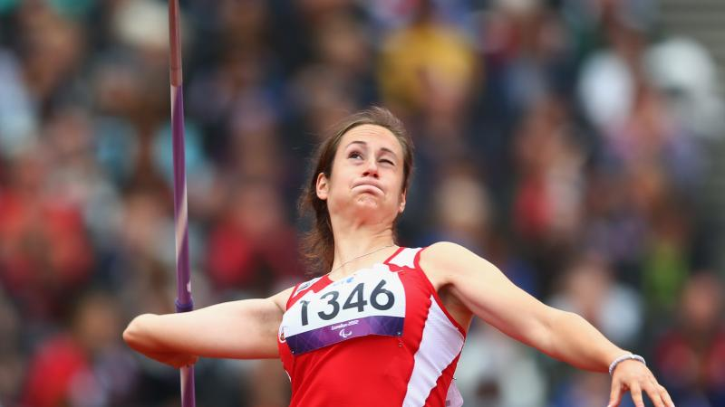 A picture of a woman in the field throwing the Javelin