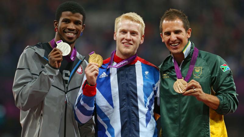 A picture of men on a podium with medals around their neck