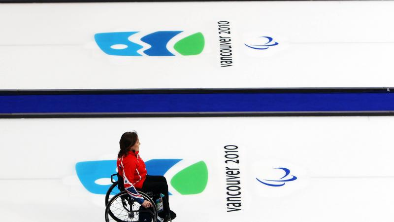A picture of a woman in a wheelchair playing curling