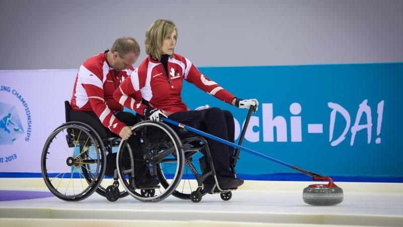 A picture of 2 person in wheelchairs playing curling