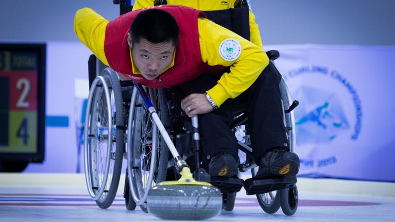 A picture of a man in a wheelchair playing curling
