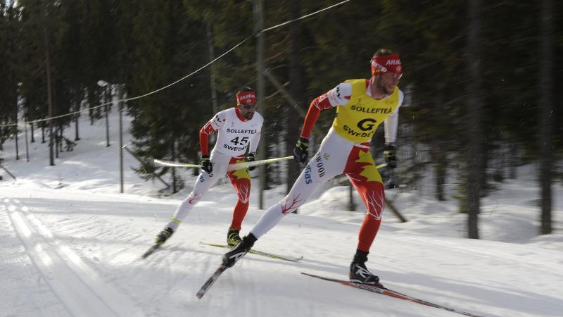 A picture of men skiing on a track