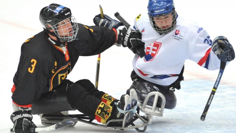 A picture of two men in sledge playing ice hockey