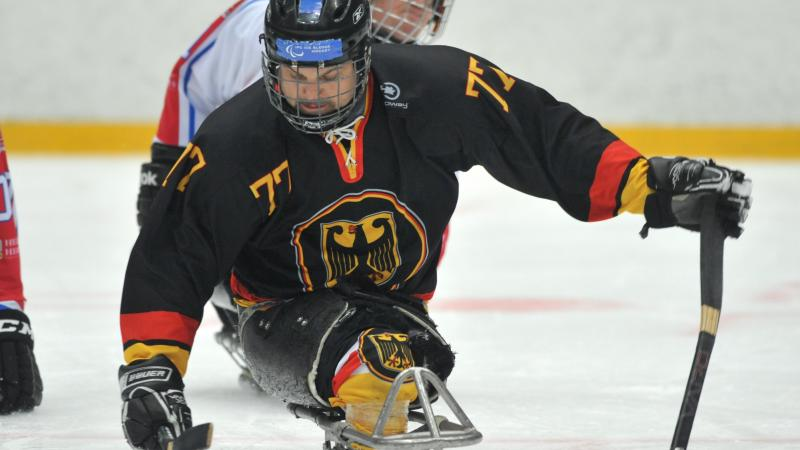 A picture of a man in ssledge playing ice hockey