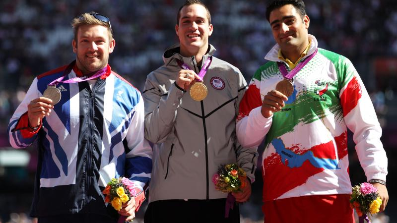 Dan Greaves, Jeremy Campbell and Farzad Sepahvand pose on the podium during the medal ceremony for the Men's Discus Throw F44 final at the London 2012 Paralympic Games
