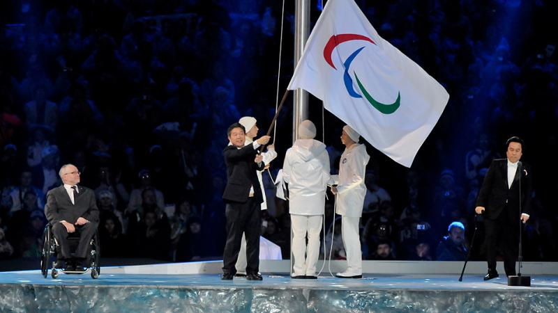 A man waves the Paralympic flag on stage