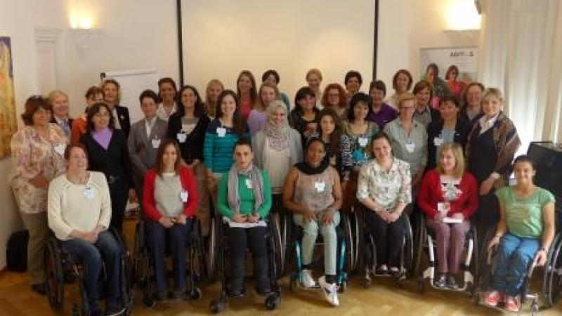 Group shot of women (standing and in wheelchairs) in front of a white wall.